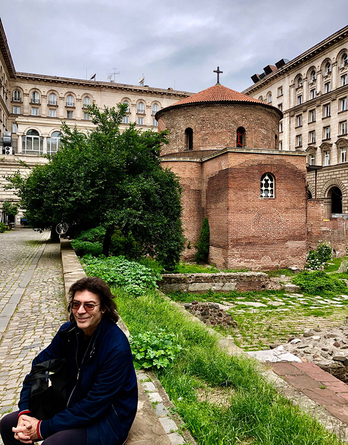 Steve with ancient Church of St Nicolas and Roman ruins