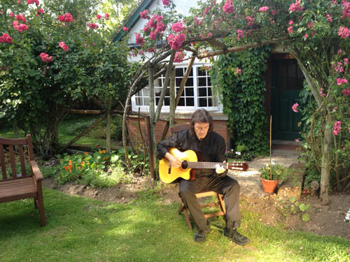 Steve playing guitar in garden of the Kilns